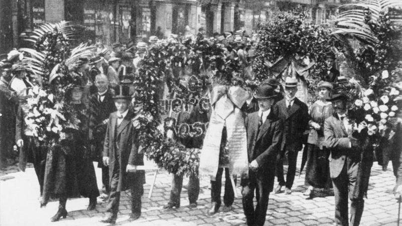 Die Beisetzung von Rosa Luxemburg am 13. Juni 1919. Riesige Kranzspenden am Anfang des Trauerzuges. Foto: Bundesarchiv