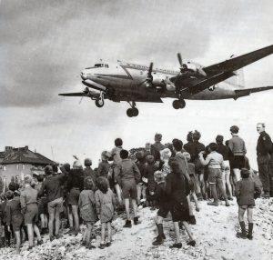 """Berliner*innen beobachten die Landung eines """"Rosinenbombers"""" auf dem Flughafen Tempelhof (1948). Foto: Henry Ries."""