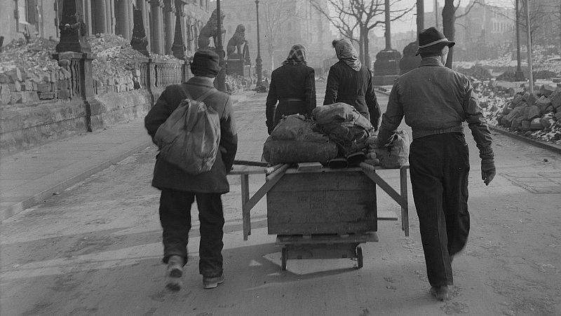Zwei Frauen und zwei Männer transportieren einen Tisch und andere Utensilien auf einem Handwagen entlang der Ostseite des Neuen Rathauses. Foto: Deutsche Fotothek